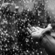 Hand im prasselnden Regen ohne Regenschirm