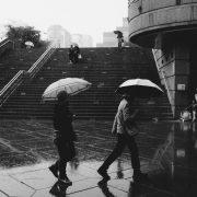 Passanten mit Regenschirmen hasten durch eine städtische Umgebung