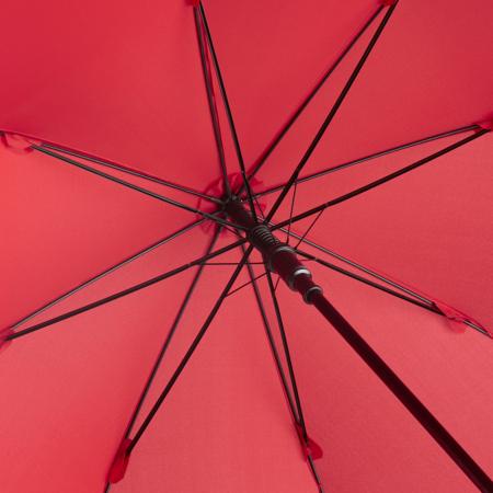 Detailaufnahme von Stahlstock und Fiberglasschienen eies Regenschirms mit rotem Bezugstoff