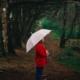 Frau steht mit einem aufgespanntem Regenschirm im Wald